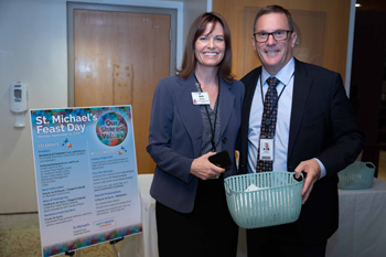 Beth Johnson and Tim Rutledge greeted staff as they arrived for work on St. Michael's Feast Day