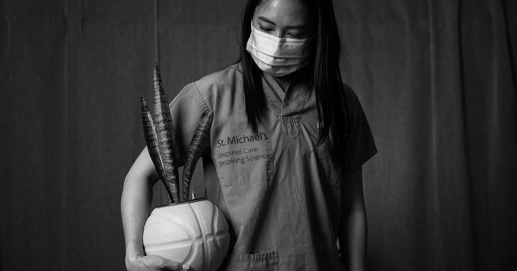 Olivia Ho, wearing scrubs and a face mask, holds onto a basketball planter she created.